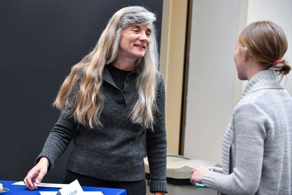 A woman with long graying hair talks to a young woman