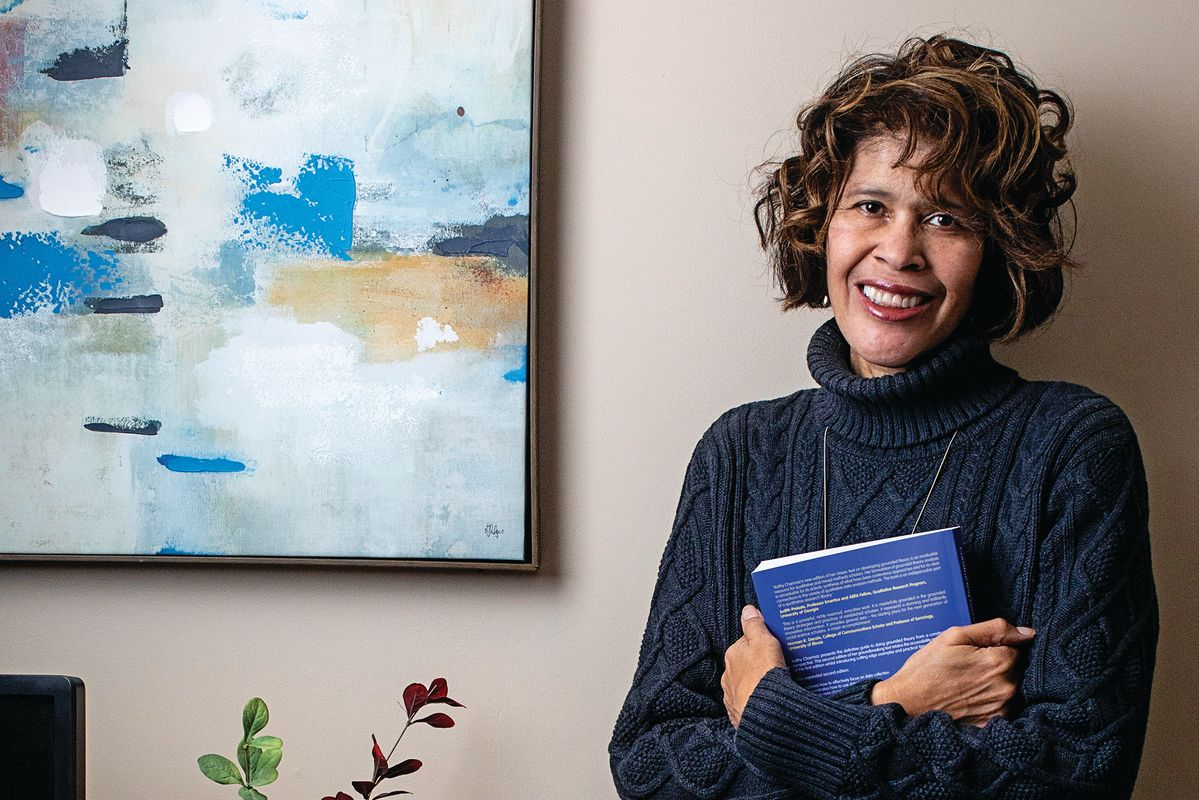 smiling woman holds book standing beside art