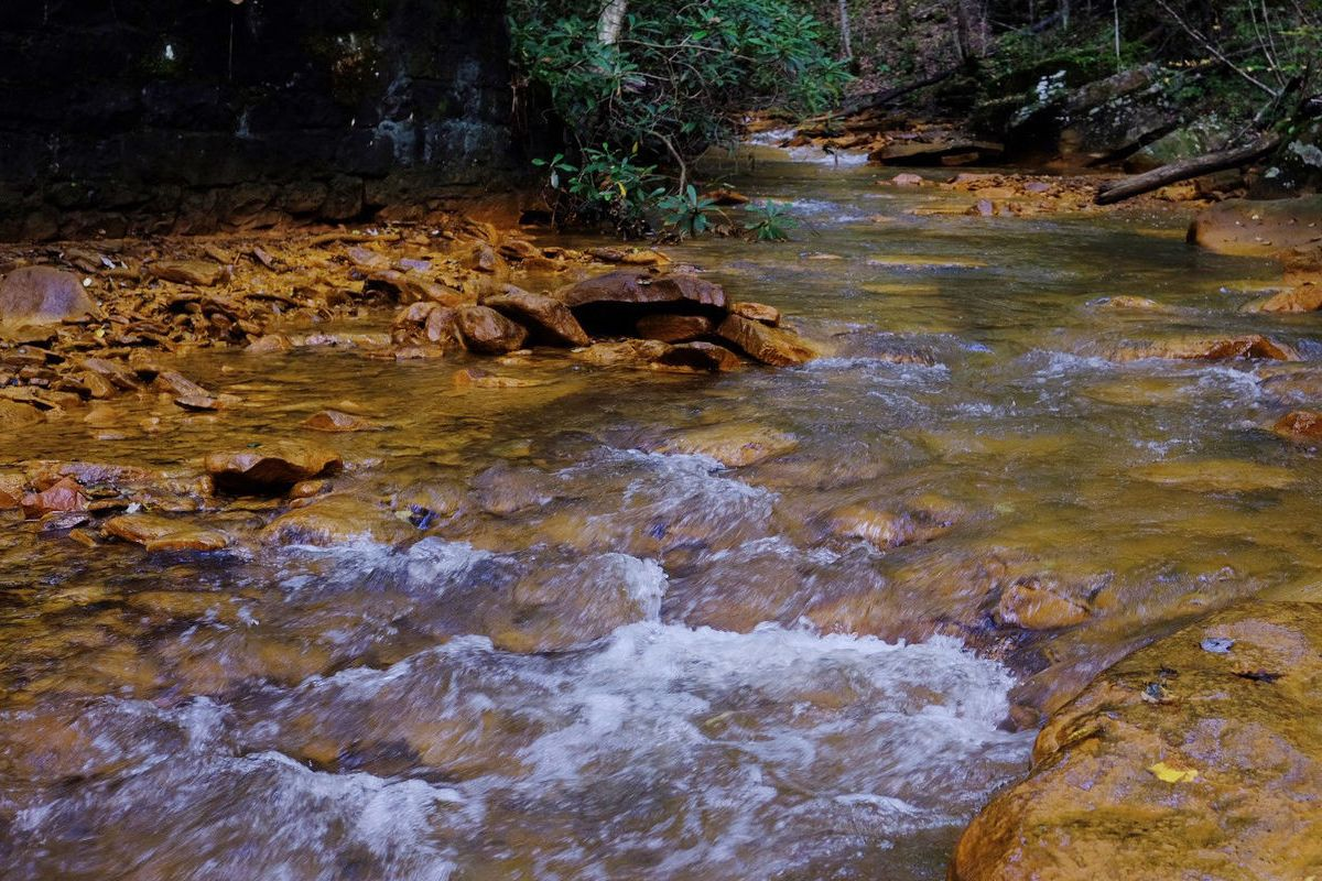 flowing stream with orange-ish residue on the banks