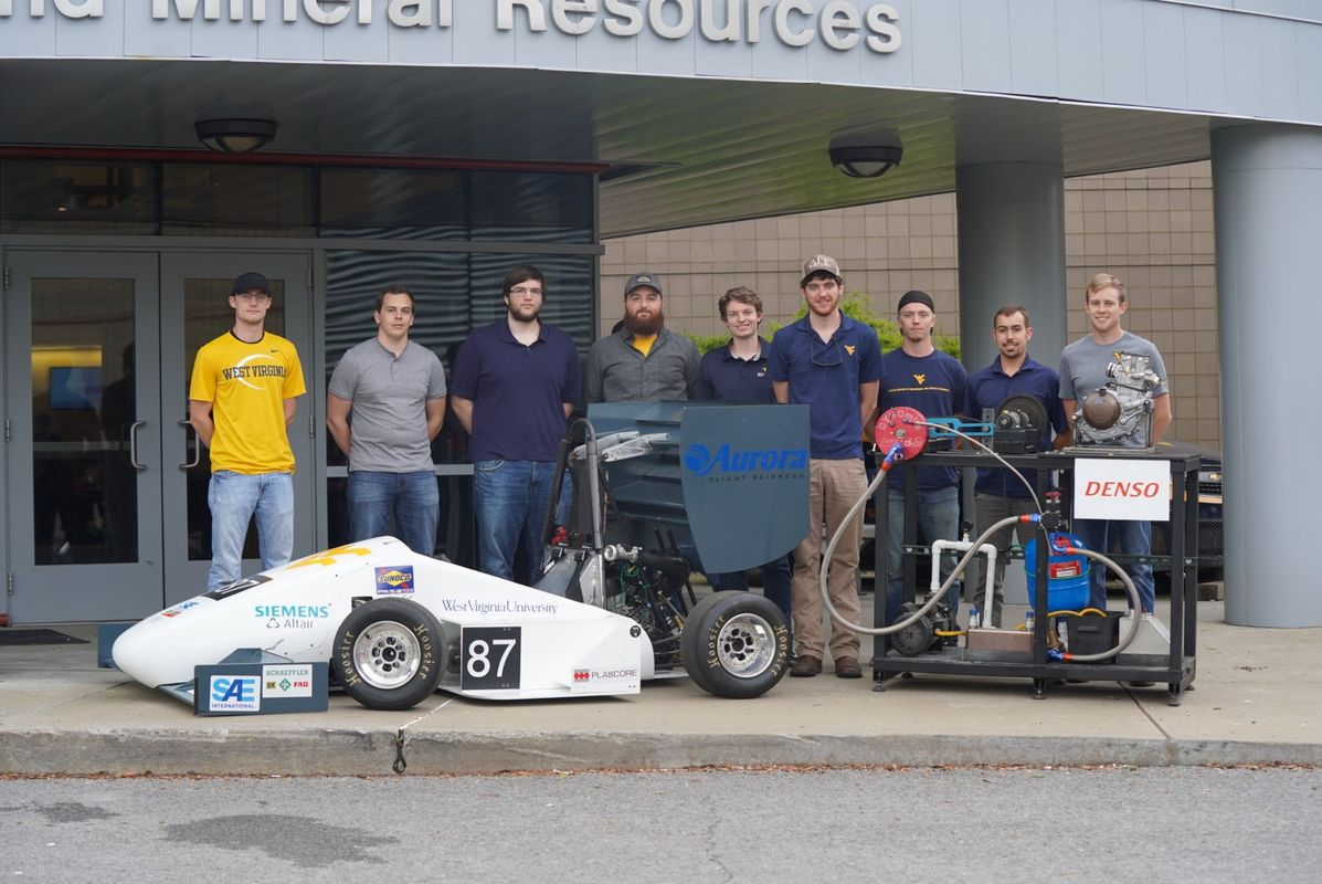 Nine men stand in front of a building showcasing the race car that they built