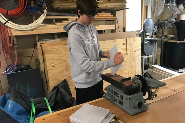 boy stands at worktable