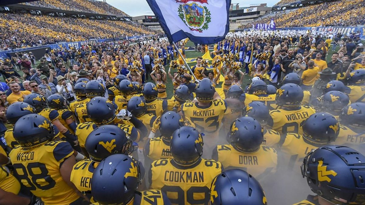 WVU football players stand at Milan Puskar stadium holding the state flag in yellow jerseys with blue helmets