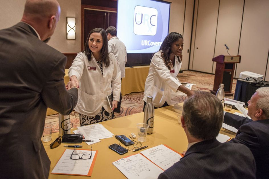 Students meet judges and shake hands in business plan competition