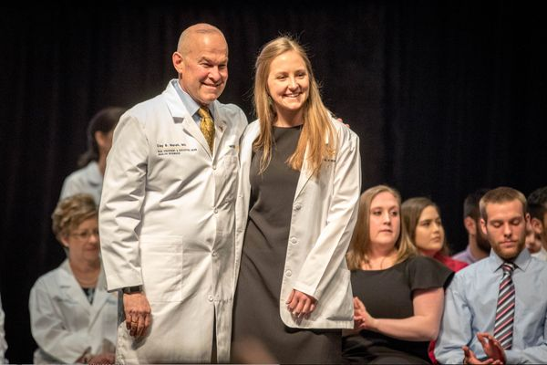 Man in a white coat stands with young woman in white coat; audience behind them