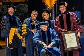 Donald Hoylman receives an HDR from WVU President Gordon Gee (R) and Dean Javier Reyes (L) at the 2018 December Commencement.