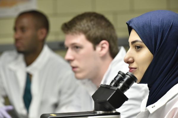 Two male students in white coats blurred in the background and a female student in a navy blue hijab and a white lab coat in focus in front of a microscope.