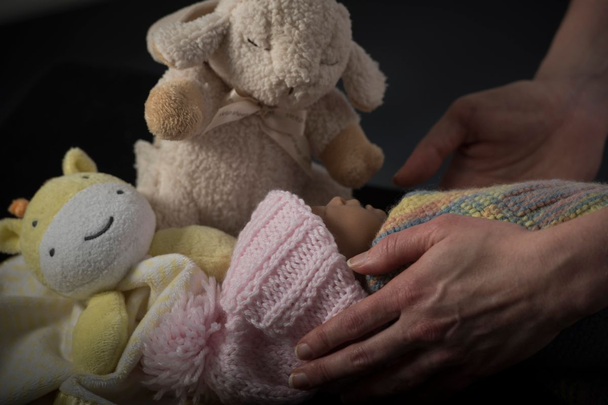 An infant wrapped in blankets and wearing a knitted hat with stuffed animals