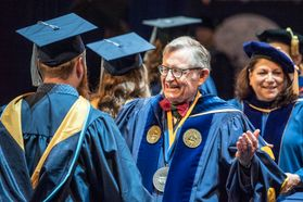 WVU President Gordon Gee congratulates graduates on the platform during December Commencement in the Coliseum Dec. 15, 2018.
