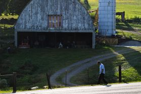 A man walks in the shadows on a dirt road by a barn