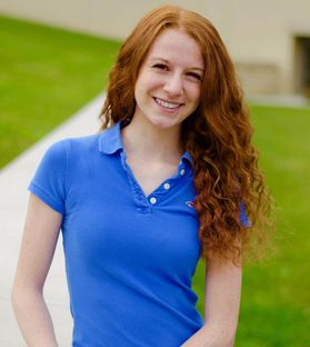 Girl smiling in blue shirt.