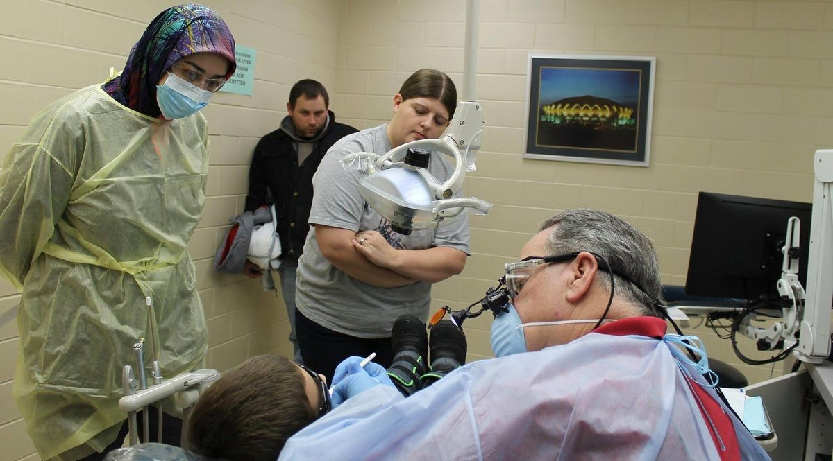 Child receives dental care while parents and dental student observe