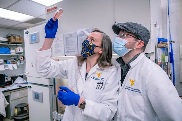 people in lab coats look up at a test tube
