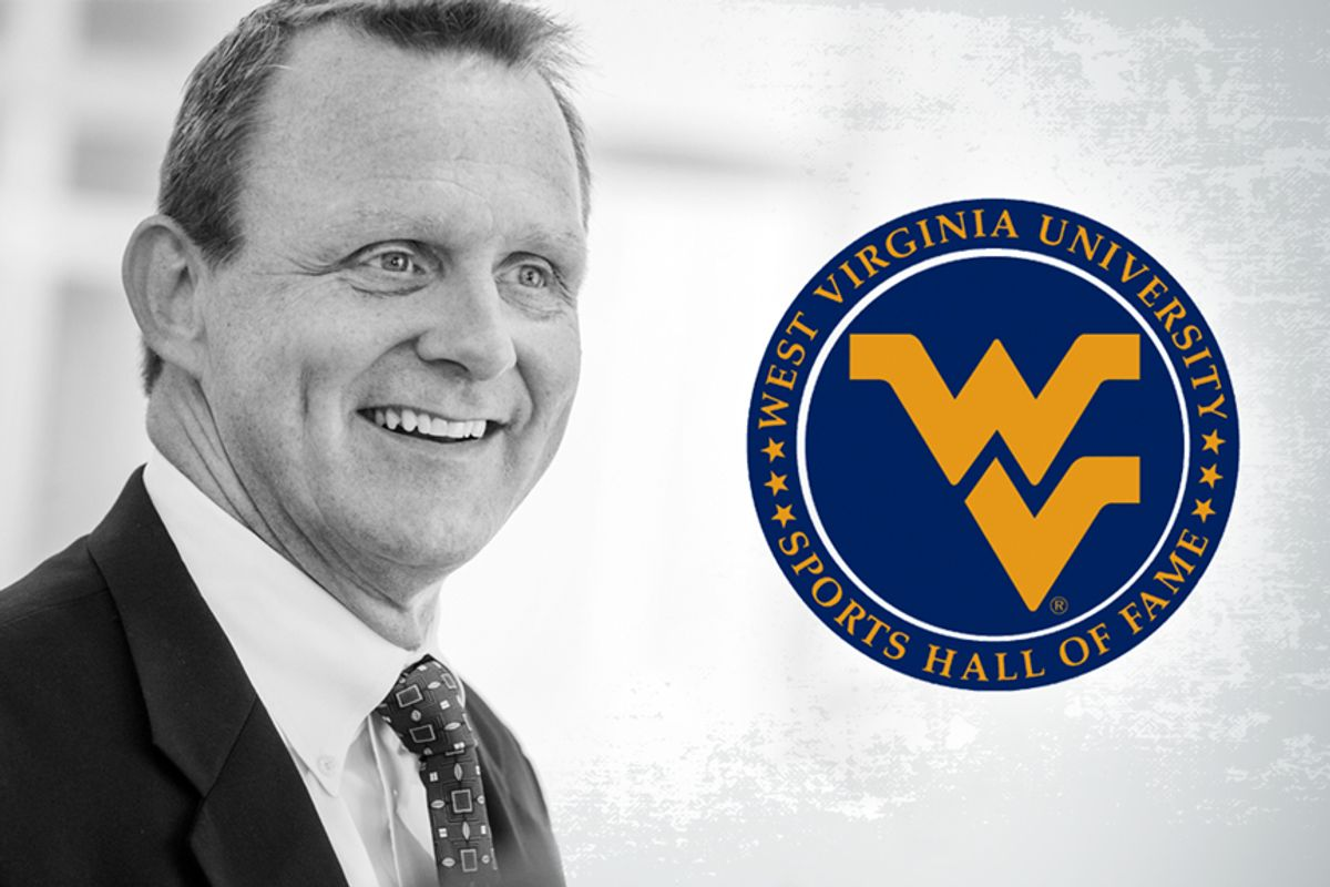 photo of smiling man left of blue and gold emblem