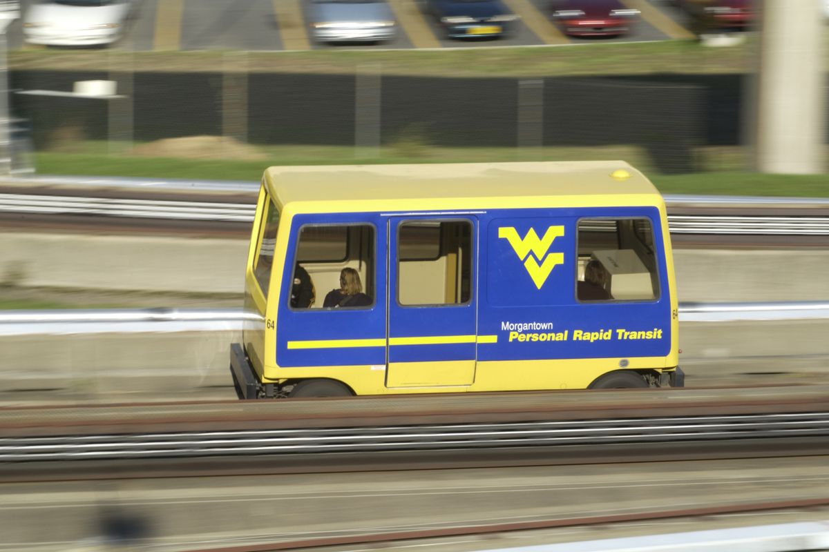 Shot of a blue and gold WV personal transit going by on the tracks.