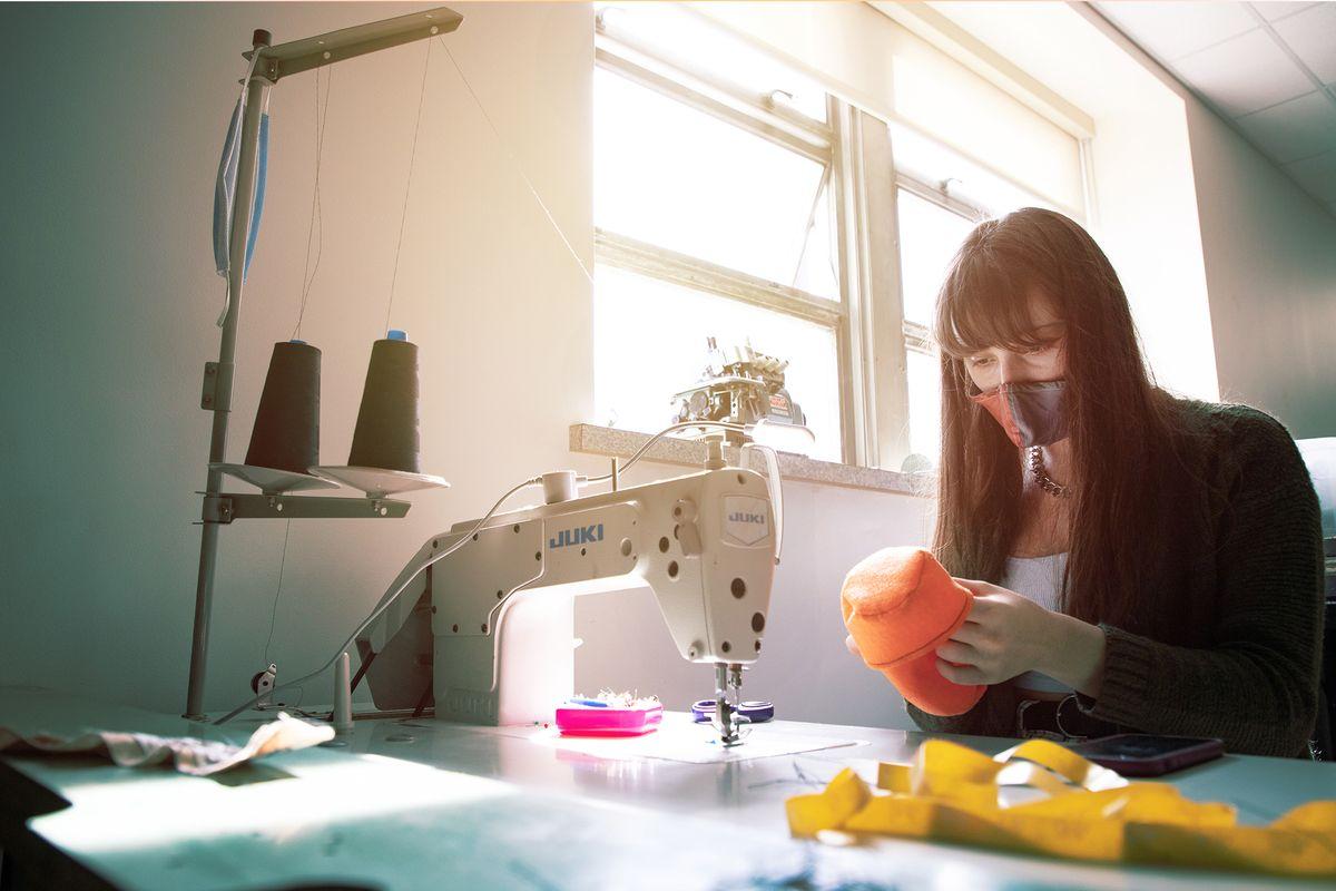 woman sits at sewing machine, wearing mask
