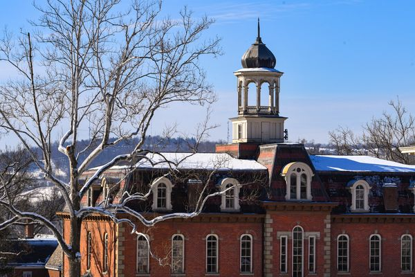 large brick building with cupola, snow on the roof