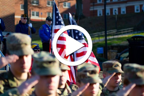 soldiers salute in front of flags with play button super-imposed