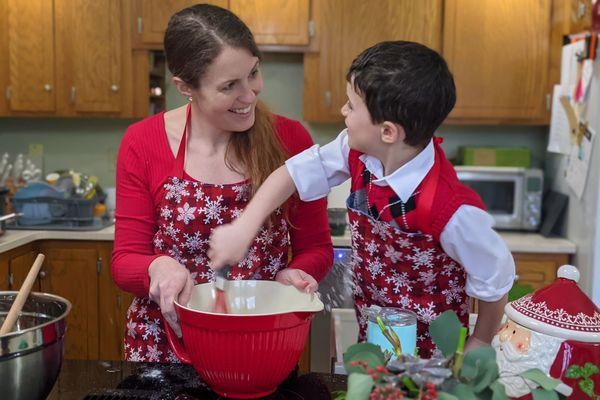 A woman and young boy posed while mixing ingredients into a bowl