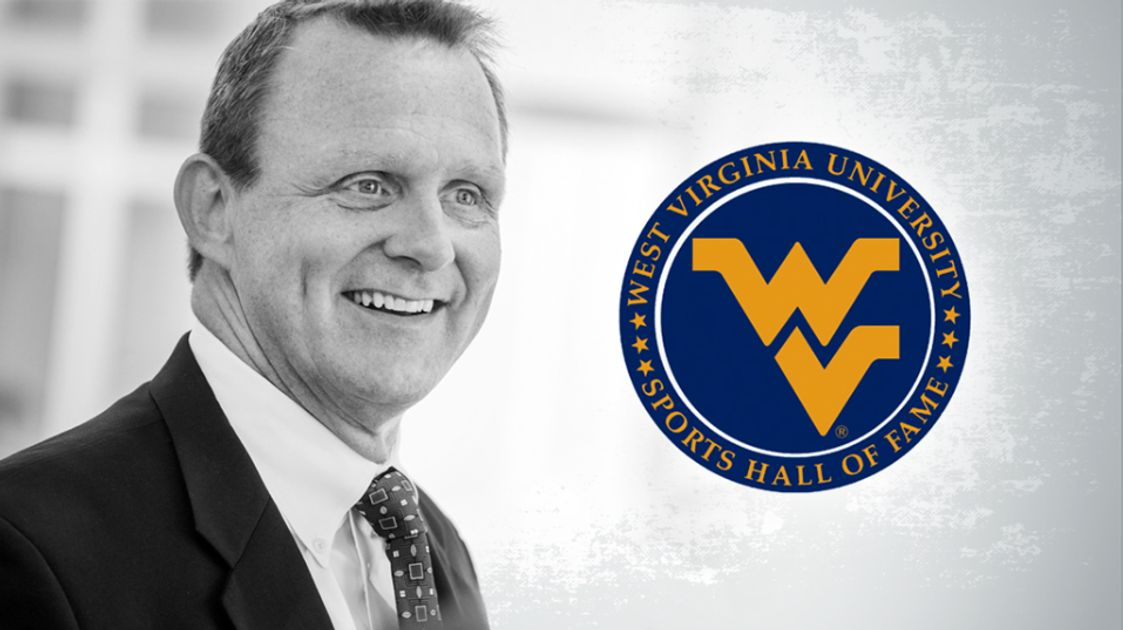 Black and white picture of man in suit with a blue and gold flying WV logo on the right
