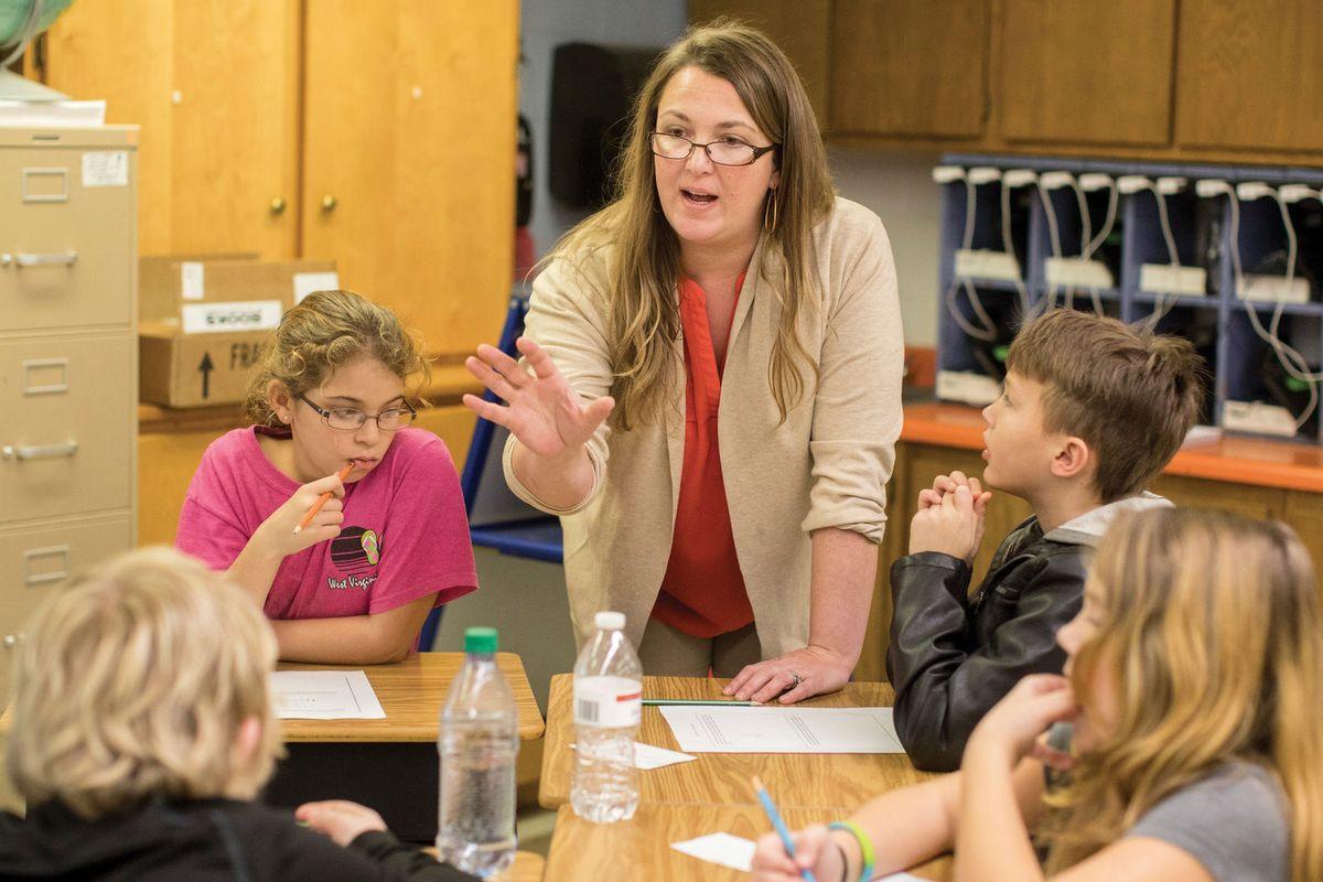 female teacher teaching group of elementary students