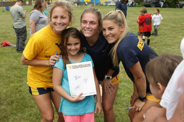 Members of the WVU women's soccer team visit with McDowell County 4-H Soccer League