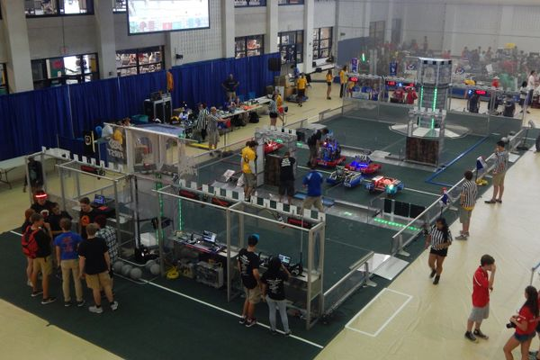 Students stand around a gray mat with machinery and robots in the WVU recreation center