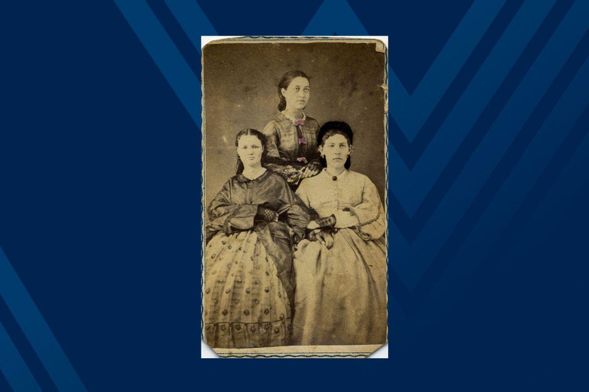 Black and white photo of three women posing.