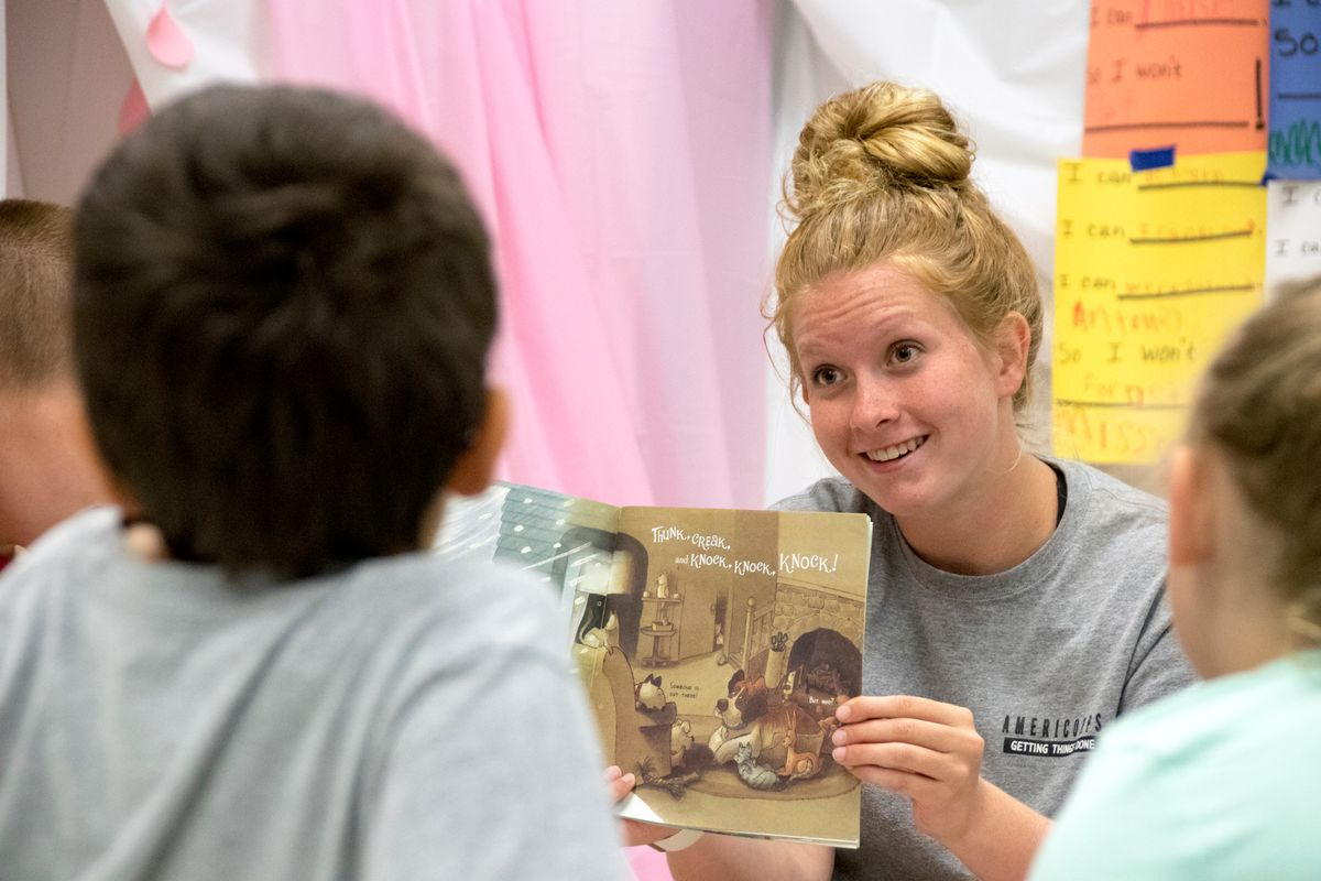 A blonde woman with her hair in a bun reads to students