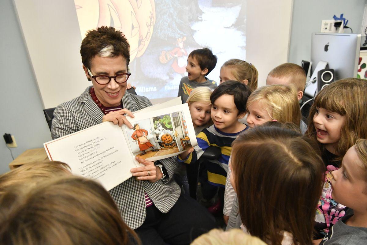 woman with short dark hair reads to children