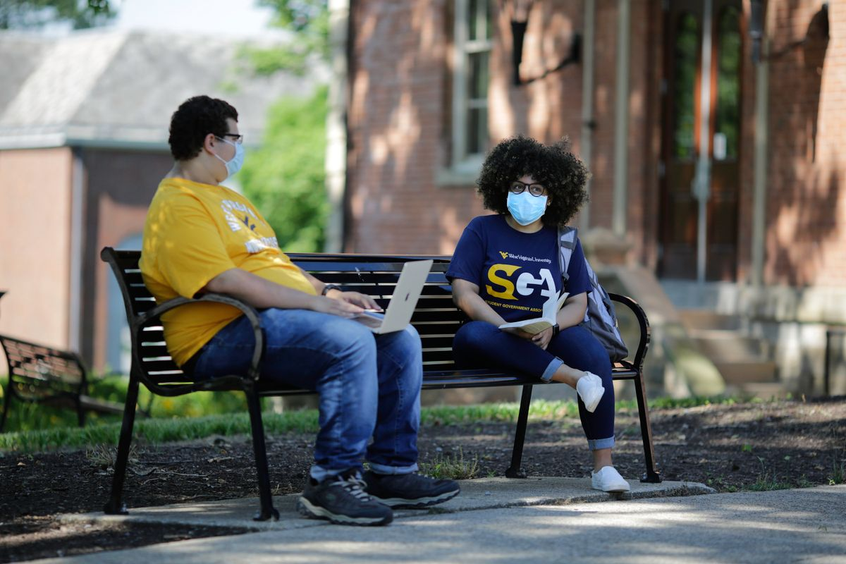 two students sit on a bench outside with masks on