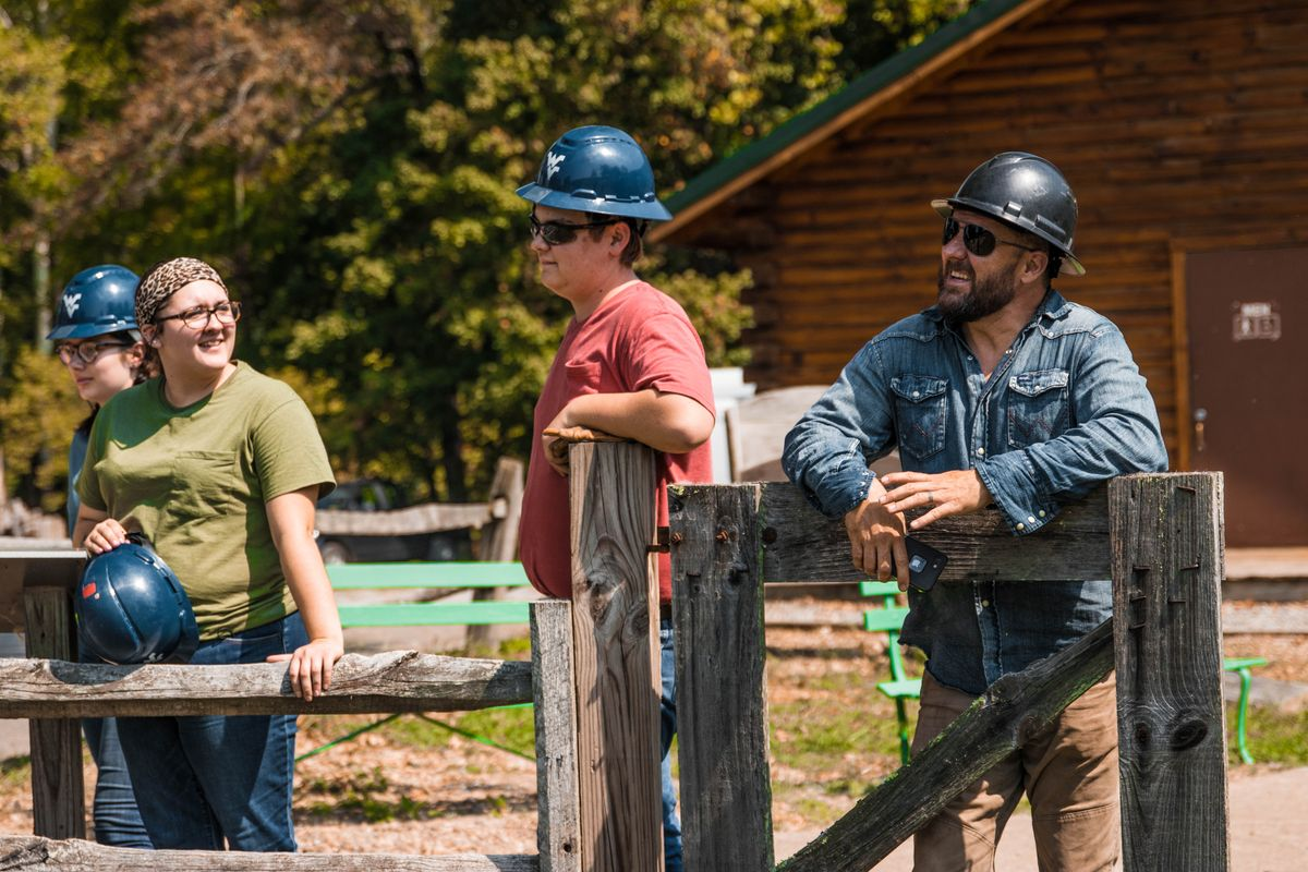 woman and two men stand in hard hats along a wood fence