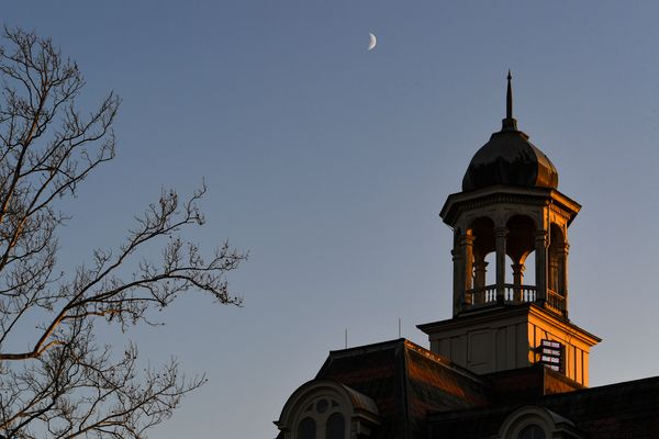 Crescent moon shown over top of building