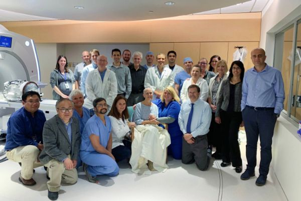 The team from the WVU Rockefeller Neurosciences Institute, led by Ali Rezai, M.D. (standing, ninth from left), poses for a picture with Judi (seated, front row), the first patient in the world to undergo focused ultrasound as part of the phase II clinical