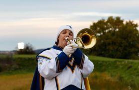 a young girl in a white hat and WV marching band uniform walks towards the camera playing a trombone