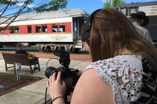 Woman with brown hair stands behind a camera at a train station