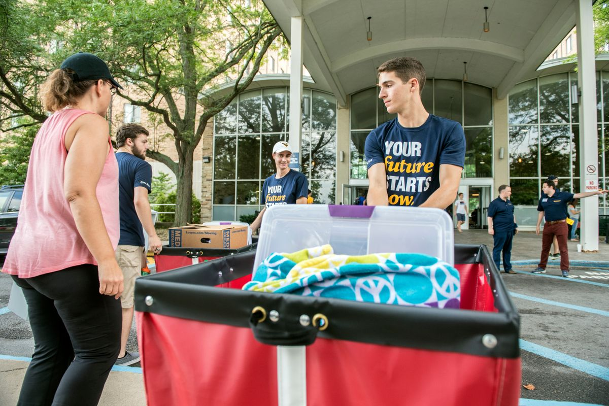 Boy in navy shirt helps mother and son move into dorm building while hauling a red cart with their stuff.