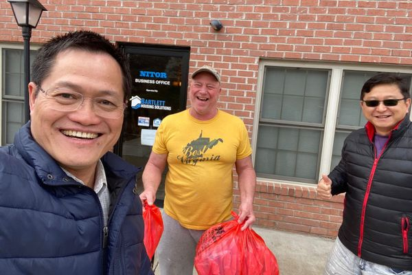 three smiling men carrying red bags of medical supplies outside a brick building