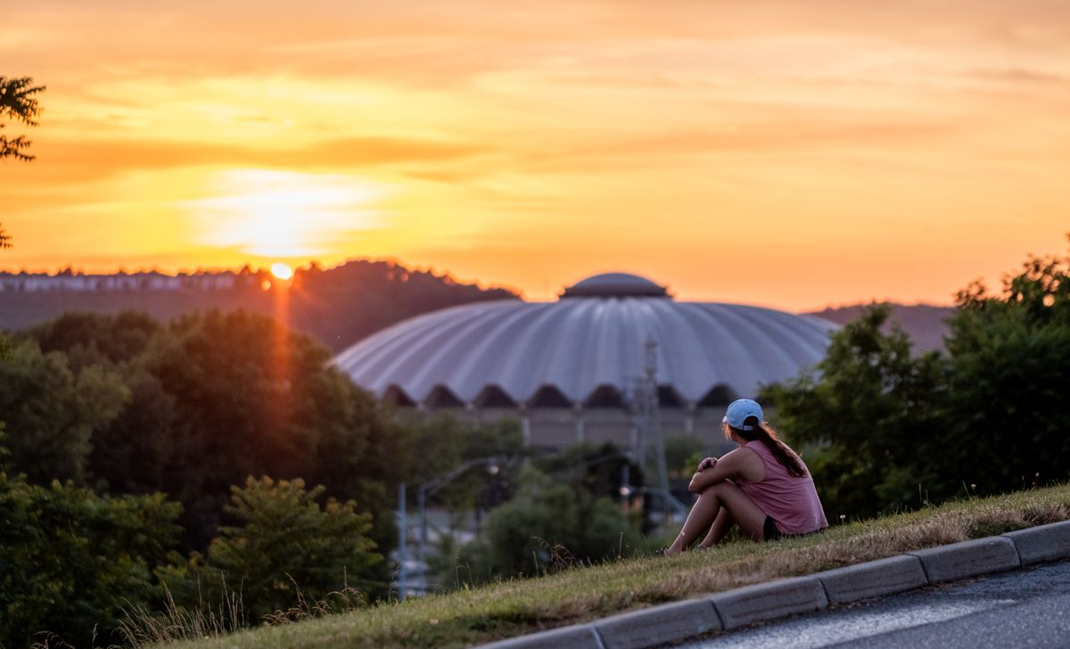 Girl sitting on a curb over looking a stadium