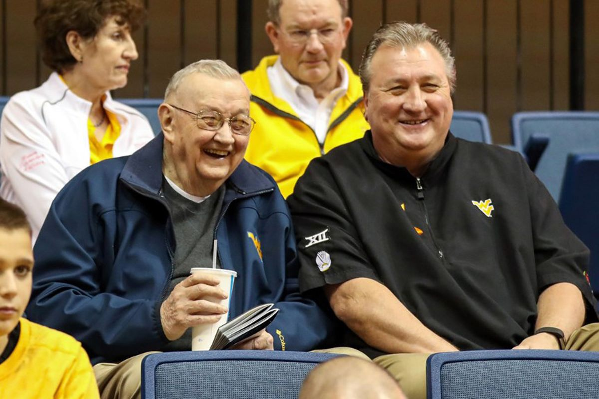 two older men sitting in stands