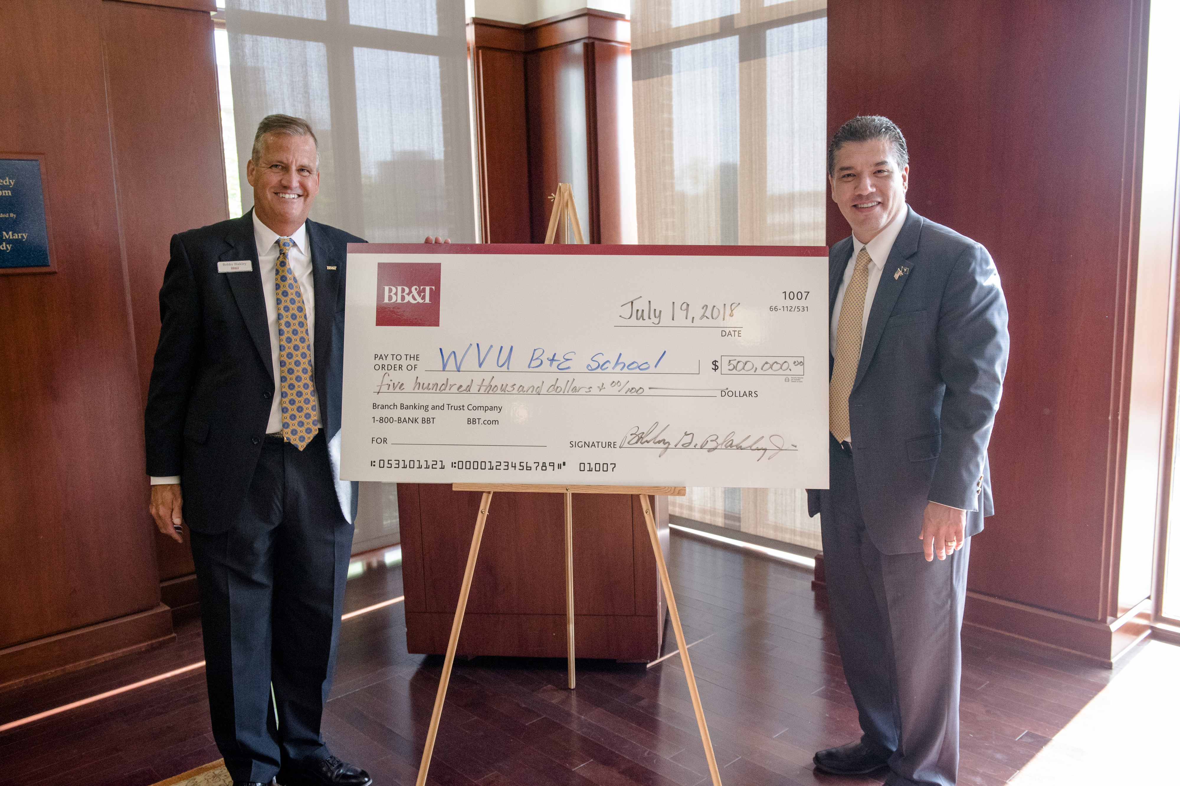 Two men flank a large check for $500,0000 situated on an easel