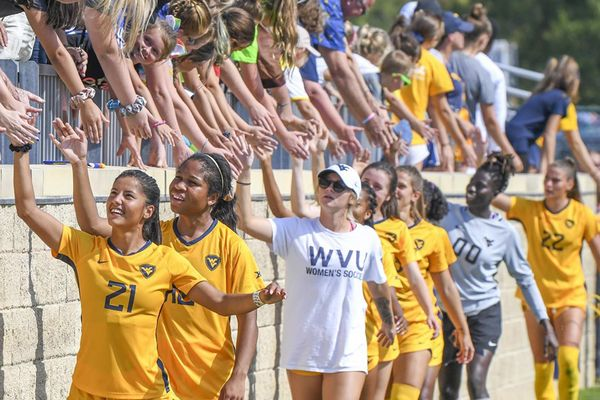 young women athletes shake hands with crowd