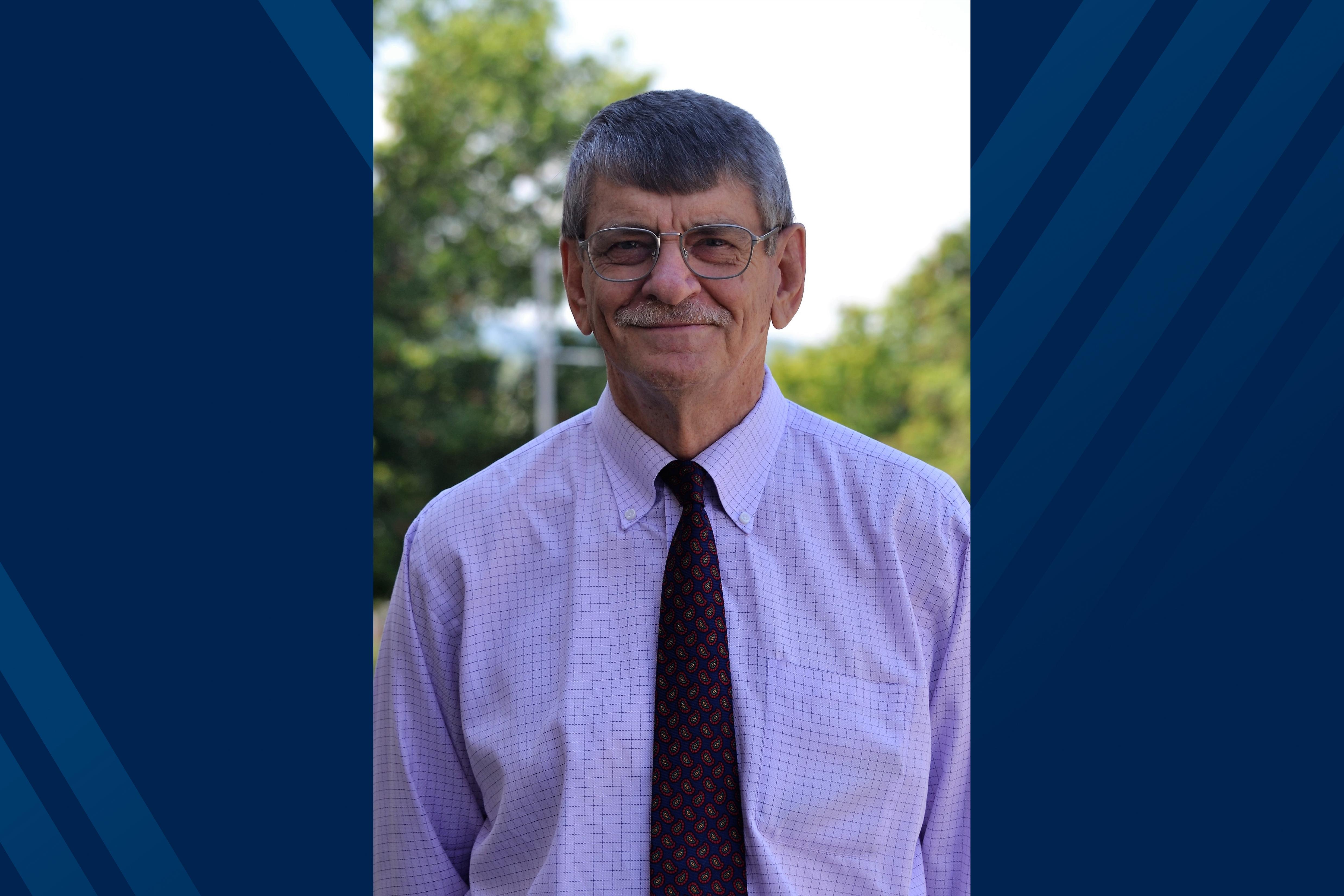 Portrait of Dr. Ian Rockett on blue background
