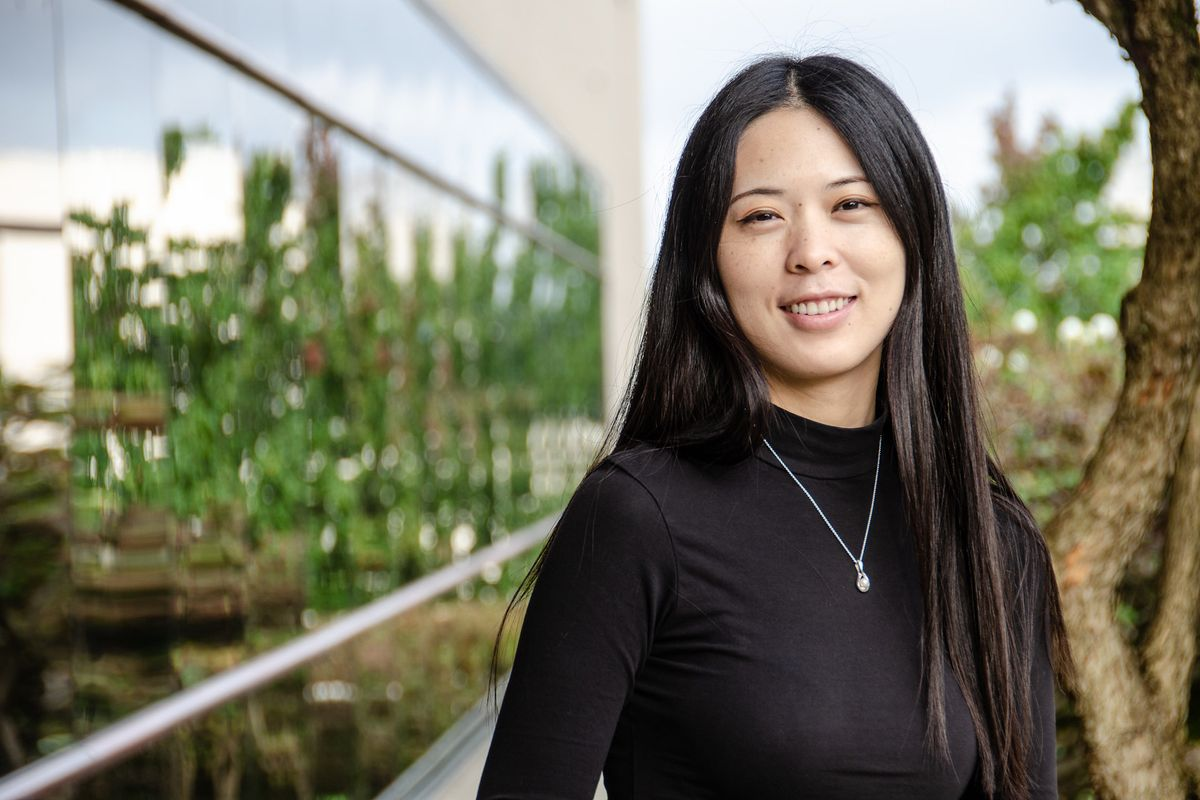 woman with black hair in a black shirt poses outside for a photo