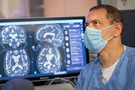 man in medical mask with computer screen of brain images in the background