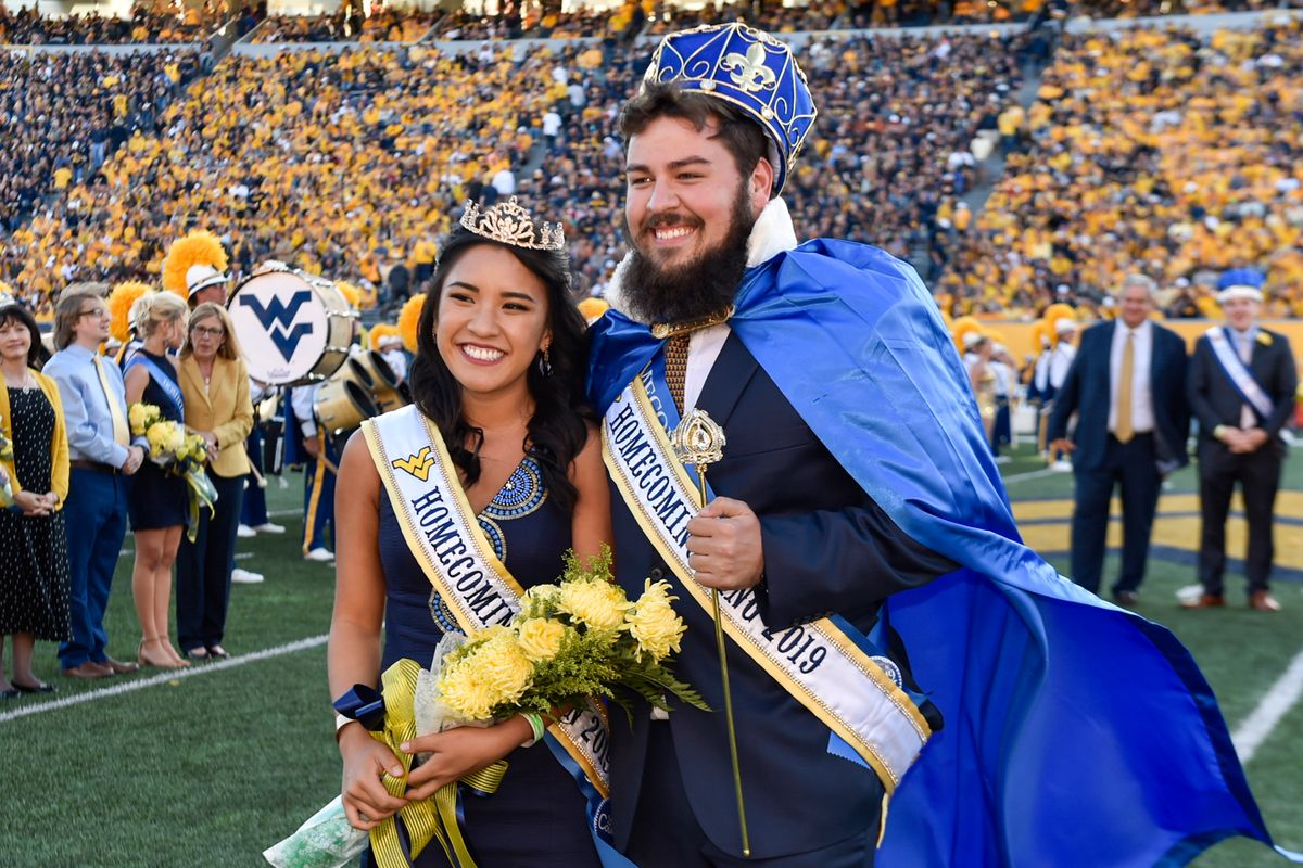 young woman and young man in homecoming crowns, capes, regalia