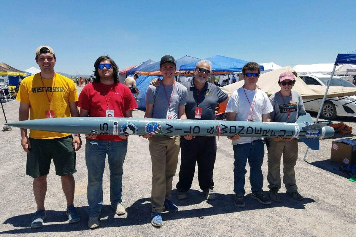 six males holding a large blue tube in front three mountain peaks