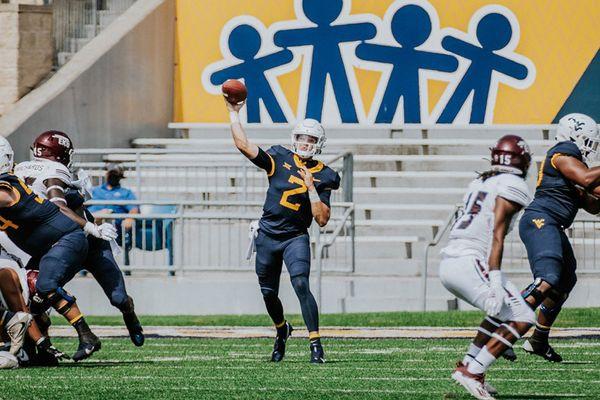 man in uniform throws football