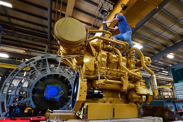 Man standing on top of large engine.