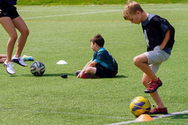 child with soccer ball, child sitting, legs and soccer ball