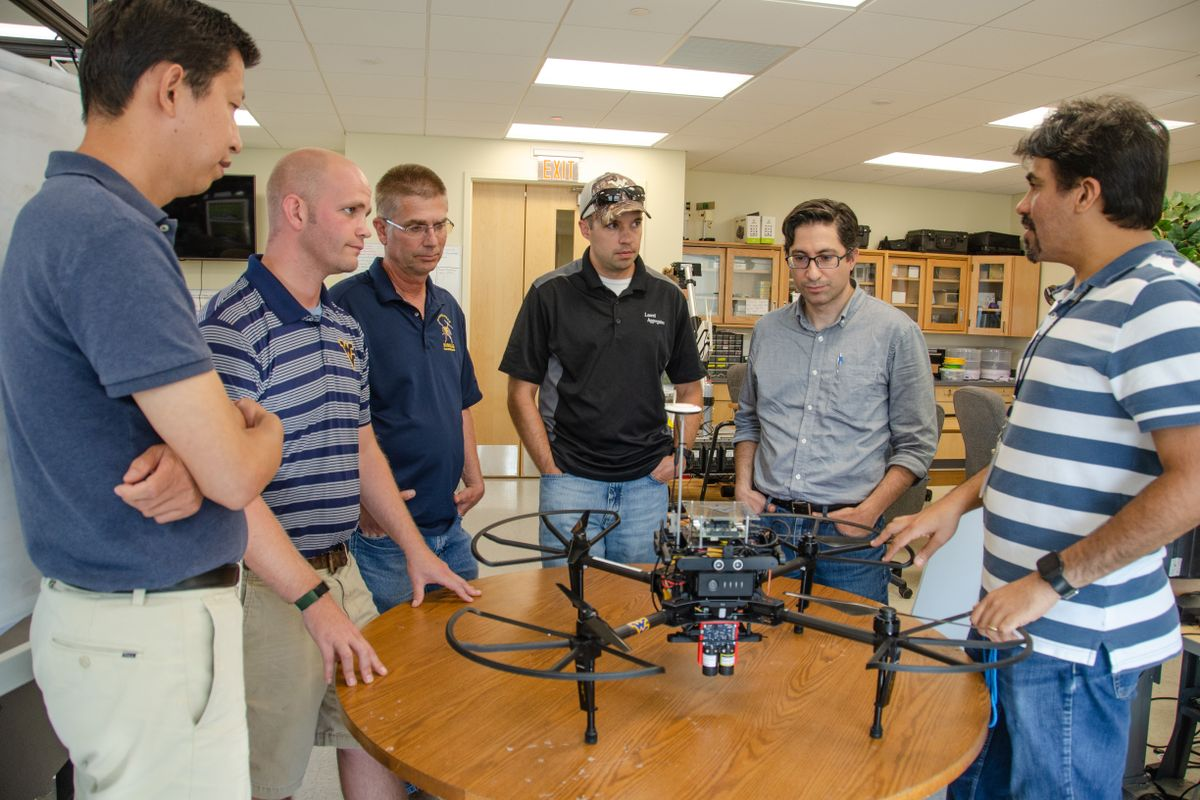 men stand around table looking at drone
